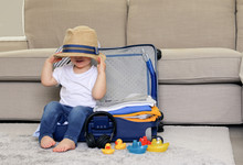 Cute Funny Little Baby Boy Siiting In Blue Suitcase With Hat On His Eyes, Packed For Vacation Full Of Clothes Ready For Traveling. Vacation With Child.