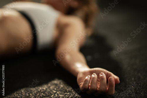 Obraz Close up of exhausted athlete resting on the floor after sports training. - fototapety do salonu