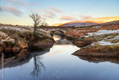 Cadres-photo bureau Brun profond Pont Ar Elan, Elan Valey, wales snowy scene of Afon Elan flowing through a bridge in winter with lone tree reflected in water and early morning sun lighting the top of distant mountains