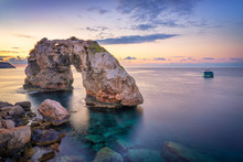 Es Pontas In Mallorca With Boat Anchored Nearby In The Mediterranean Sea. Majorca Sunrise With Yacht And Rock Arch Near Santanyi.