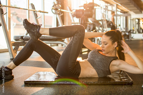 Fotografie, Obraz  Fitness girl doing bicycle crunch exercise on exercise mat in gym