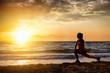 canvas print picture - Silhouette einer sportlichen Frau bei Stretching nach ihrem Training am Strand bei Sonnenuntergang