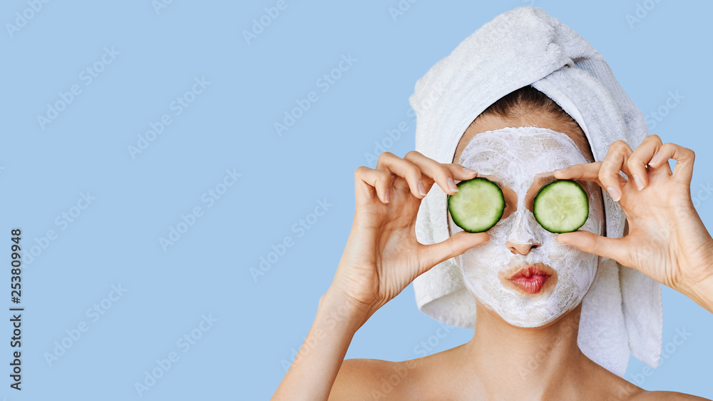 Fototapety, obrazy: Beautiful young woman with facial mask on her face holding slices of cucumber. Skin care and treatment, spa, natural beauty and cosmetology concept.