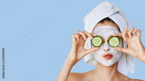 fototapeta na ścianę Beautiful young woman with facial mask on her face holding slices of cucumber. Skin care and treatment, spa, natural beauty and cosmetology concept.