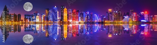 Fényképezés  Banner panorama of Doha West Bay skyline lighting by night reflecting in Doha Bay