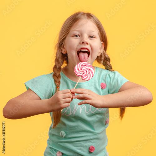 Photo  Cute little girl licks candy and laughs in the studio on a yellow background