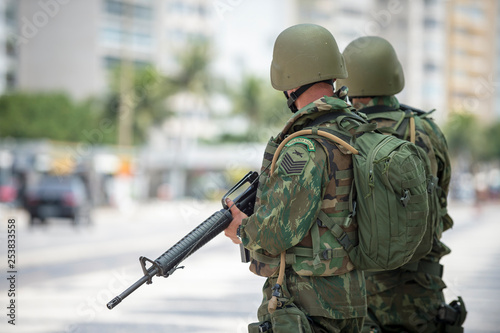 Fotografie, Obraz  Two Brazilian Army soldiers standing in full camouflage uniform on the boardwalk