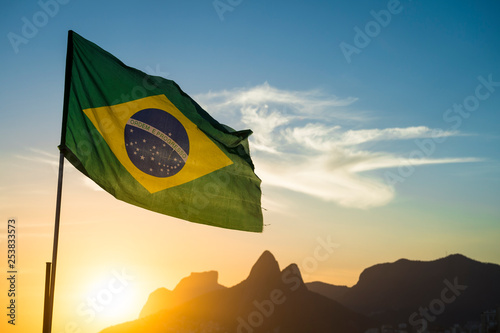 Fond de hotte en verre imprimé Brésil Brazilian flag waving backlit in front of the golden sunset mountain skyline at Ipanema Beach in Rio de Janeiro, Brazil