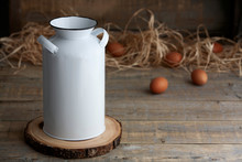 Mockup Of A White Vintage Milk Jug Next To Fresh Eggs And Straw On A Brown Wooden Table.