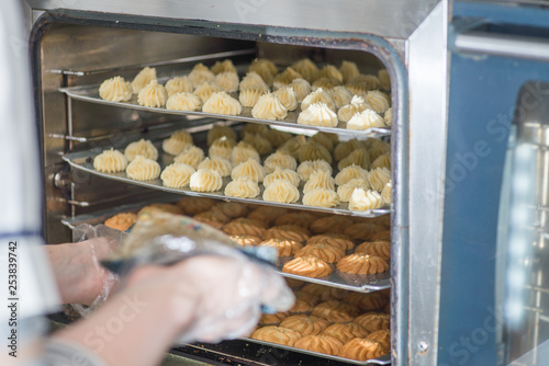 Deurstickers Bakkerij baker puts in the oven a baking tray with baking, Industrial production of bread bakery products