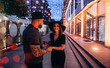 Couple in black hats are walking in the evening city
