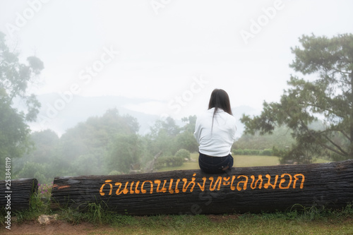 Women wearing a white shirt sitting on a stick,Looking at the sea of fog Canvas Print