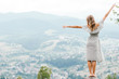 Leinwandbild Motiv Young beautiful barefoot blonde girl with long hair in summer dress standing on top of conquered mountain at stone and enjoying fabulous landscape scenic view with mountains and village in valley