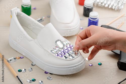 Fotografía  Girl adding rhinestones to shoes