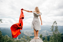 Woman In Wild Mountains Gives Distress Signal SOS Using Red Cover. Concept Of Emergency Situation During Hike In Mountains. Barefoot Woman Stands At Stone, Waving Red Blanket And Waiting For Help
