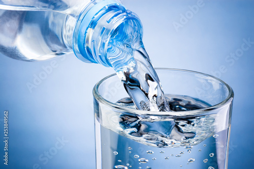Obraz Pouring water from bottle into glass on blue background - fototapety do salonu
