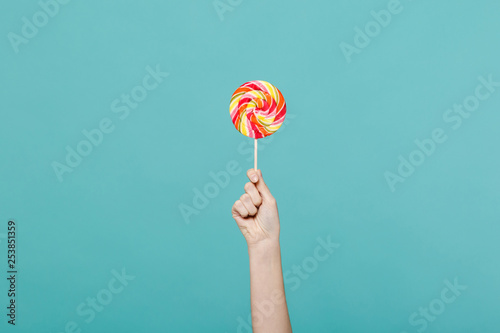 Close up female holding in hand colorful round lollipop isolated on blue turquoise wall background Poster Mural XXL
