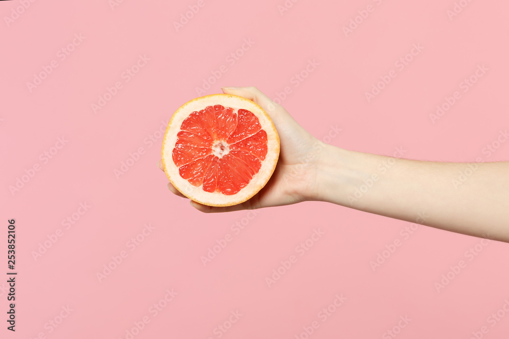 Fotografie, Obraz Close up cropped photo of female hold in hand fresh ripe half grapefruit fruit isolated on pink pastel wall background