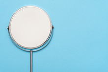 Top View Image Of Circle Hand Mirror On Blue Background.