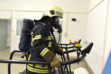 Firefighter With Respirator And Air Tank Exercising On Treadmill