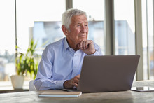 Portrait Of Pensive Senior Man Sitting At Table With Laptop Looking At Distance