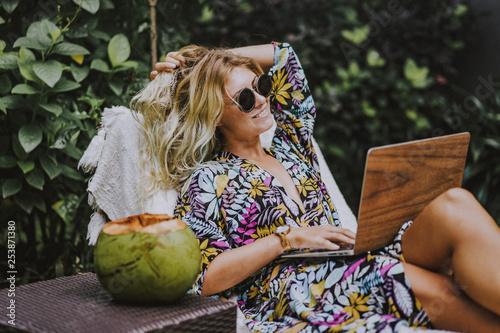 Woman freelancer, travel blogger works on a laptop Fototapeta
