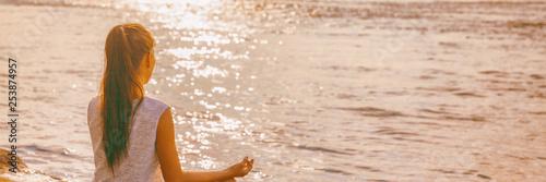 Yoga woman meditating on morning sunrise . Beach meditation banner panorama.