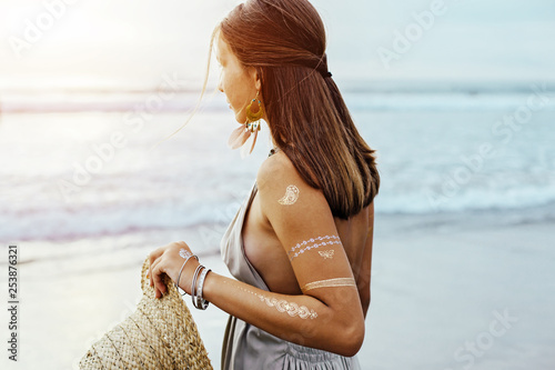 Young girl with silver tattoo and boho jewelry on sunset