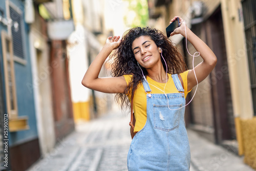 Photo sur Toile Kiev Attractive African girl listening to music with earphones outdoors.