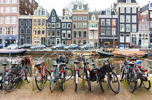 Street in Amsterdam, yachts on the canal and bicycle parking in the foreground c Wallpaper Mural