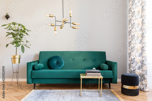 Bright and sunny minimalistic home interior with design green velvet sofa, furniture,plant, gold coffee table with books and elegant pendant lamp Poster Mural XXL