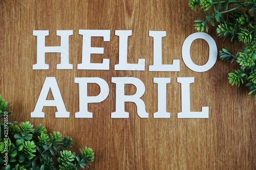 Fotografie, Obraz  Hello April Alphabet Letters with green plant on wooden background