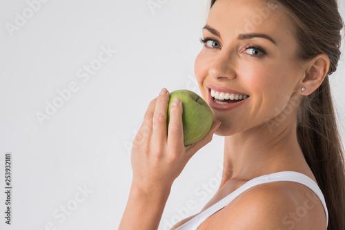 Obraz Woman biting green apple - fototapety do salonu