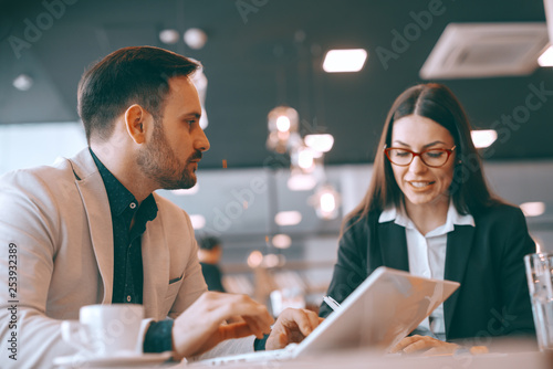 Photo  Unshaven Caucasian businessman using laptop and talking to his female colleague while sitting in cafeteria