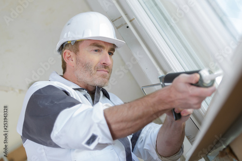 Obraz worker using a silicone tube for repairing of window indoor - fototapety do salonu