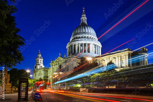 Photo Night view of the beautiful facade of St Paul's Cathedral in the City of London, London, England, with the iconic red bus passing by