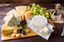Cheese Plate Served With Grapes On A Wooden Background