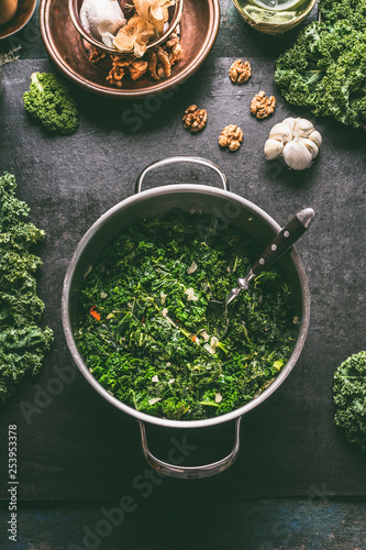 Stewed kale in cooking pot on dark kitchen table background with ingredients, to Canvas Print