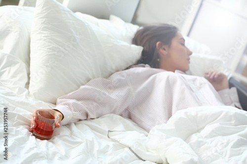 Fotografija  Young woman lying in bed deadly drunken holding near-empty bottle of booze