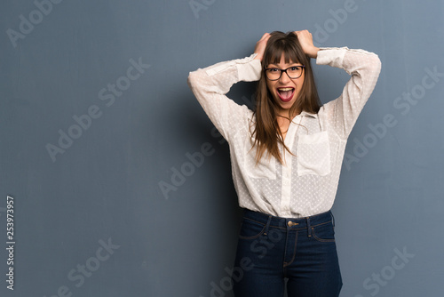 Fototapety, obrazy: Woman with glasses over blue wall with surprise and shocked facial expression
