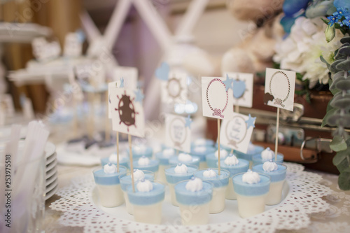 Foto blue and white christening candy bar: close up photo of pana cotta with sticks w