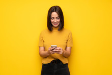 Young Woman Over Yellow Wall Sending A Message With The Mobile