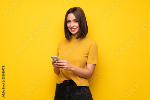 Fotografering  Young woman over yellow wall sending a message with the mobile
