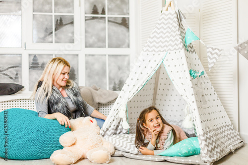 Fotografia Woman wearing cute animal house slippers sitting on the floor in handmade wigwam