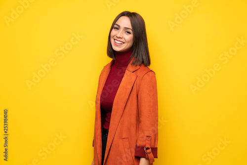 Obraz Young woman with coat smiling - fototapety do salonu