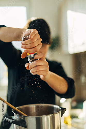 Obraz na płótnie Female chef grinding mixed black pepper in a pot