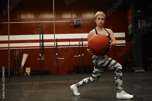 Photo  Confident strong atheltic woman with short haircut plunging in gym, using fitness accessory