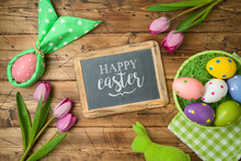 Easter Holiday Background With Chalkboard, Easter Eggs In Basket And Tulip Flowers On Wooden Table.