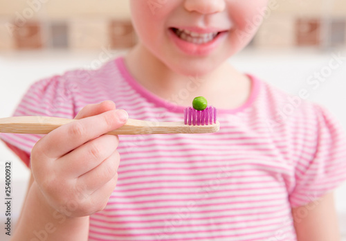 Photo Selective focus on bamboo tooth brush with green pea on it and smiling blurred anonymous girl on background