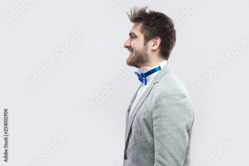Fotografie, Obraz  Profile side view portrait of happy satisfied handsome bearded man in casual grey suit and blue bow tie standing and looking straight with toothy smile